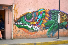 colorfull grafitti of a chameleon on entire pink wall outside the station of tren ligero of Xochimilco