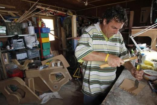 Izhar Gafni making his cardboard bike Image credit: Reuters / Baz Ratner