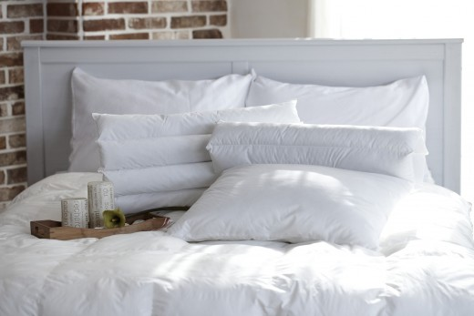 For a luxutious hotel look, make the bed with fresh white linens rather than multi-colored sheets.