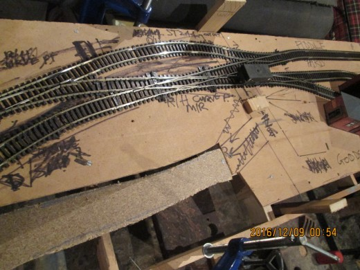 The 48 x 15 inch frame completed, risers attached to four intermediate cross-members between the frame sides, 3-ply board cut to shape and screwed onto risers. Peco track shuffled into position and assembled...