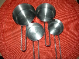 Nested metal measuring cups in 1/4 cup, 1/3 cup, 1/2 cup and 1 cup gradation.