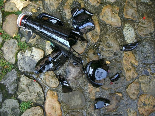 Broken beer bottle shards on grass and stone cobbles should be cleared asap.