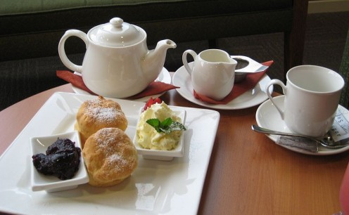 English afternoon tea-time; a pot of tea, scones, clotted cream and strawberry jam.