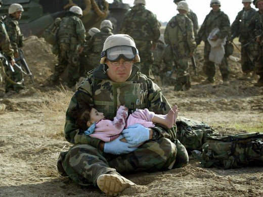 Soldier holding traumatized Iraqi girl who lost her parents.