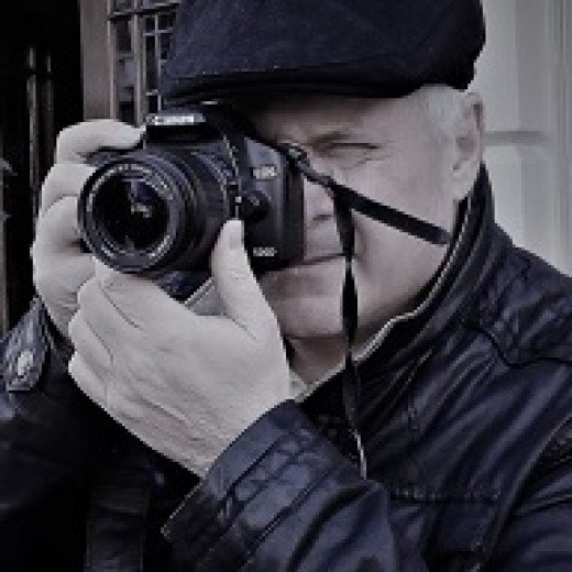 Black and white photo of molometer taking a photo with a DSLR camera wearing a flat cap