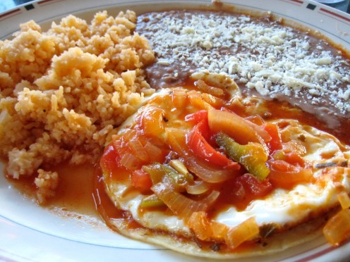This photo of ranch style eggs has the fried rice on the far left of the plate. The re-fried beans with the cheese is next followed by salsa, fried eggs, and the tortilla.