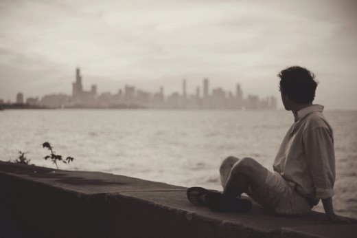He is sitting alone, feeling lonely in long distance relationship and waiting for the day when she will come.