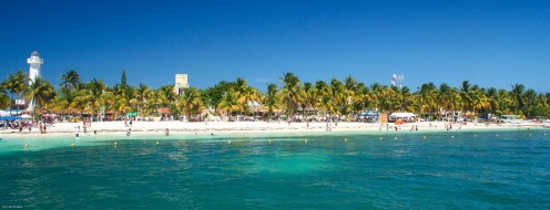 A view of a beach in Cancun, Mexico as the area is surrounded by many trees and sand as well. Although it is known for its humidity in the summer months, Cancun is a very popular tourist destination.