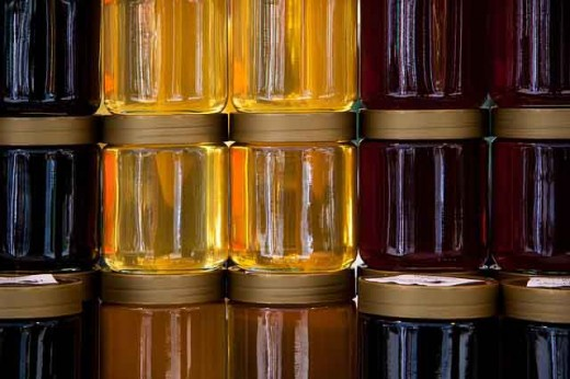 Jars of honey on a shelf waiting to be labeled.