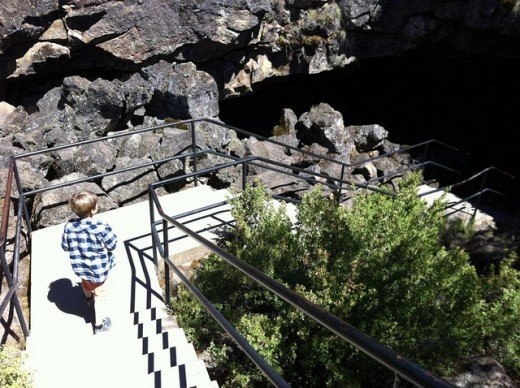The bright, sunlit stairway to the cave entrance gives no clue to the pitch blackness within .