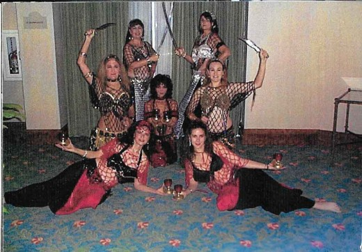 "Costumed tribal fusion dancers using swords, daggers, and candles in their ""fusion"" dance choreography."