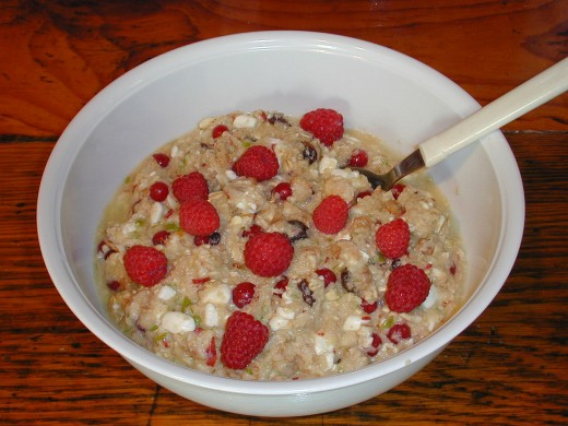 Bowl of overnight soaked oats, made from rolled oats, orange juice, low-fat milk, apple, banana, red currants, raisins and yogurt. Fresh raspberries were added just before serving.