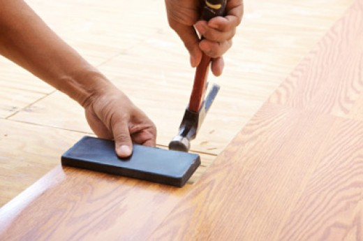 Fixing laminate flooring joints with the help of tapping block and hammer.