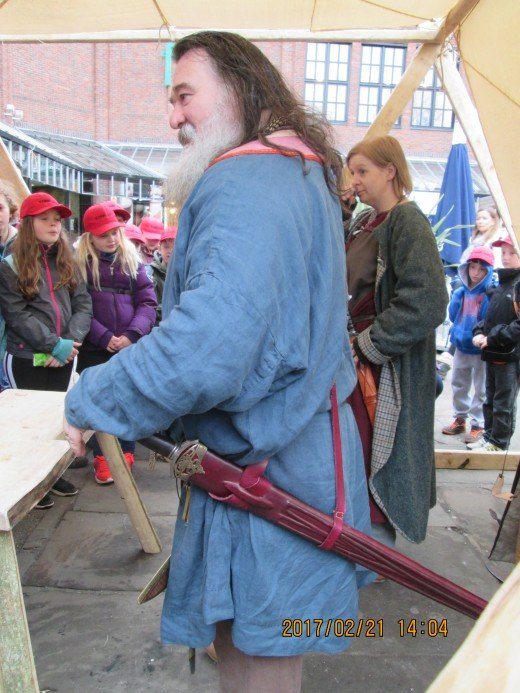 Meet the Jarl, Norse equivalent of Earl, as he engages a youthful audience to inform them of a re-enactment. The girl behind him, from Glasgow, has taken on the guise of a woman skald. Not just men travelled between settlements with sagas to tell
