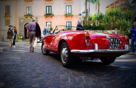 A clean and shiny red Alfa Romeo Spider car gets admiring glances from passers-by.
