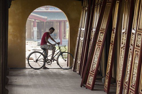 A cyclist views wooden doors in the Imperial palace in Hue‎, Vietnam.
