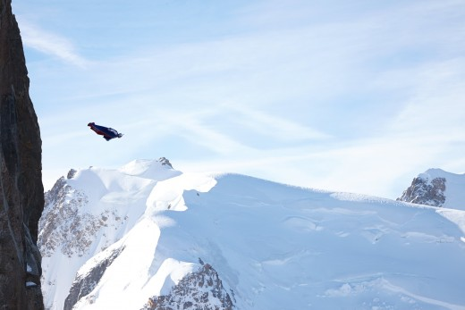 A wingsuit flyer glides over snow covered mountains.