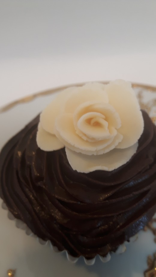 White modeling chocolate rose on chocolate frosted cupcake.