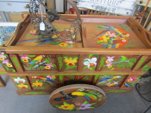 - Parrot portraits decorate a wooden cart on sale at a Buzzards' Bay, MA antique store. - Photo by George Sommers