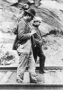 Two hobos walking along railroad tracks after being put off a train. One is carrying a bindle.