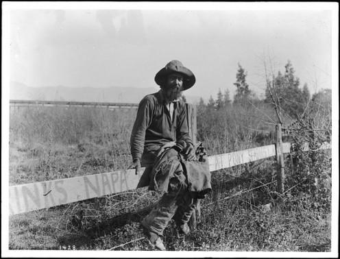 Photograph of a ragged hobo sitting on a fence circa 1920