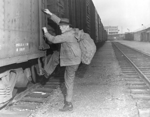 A man hitching a freight train who might be venturing from town to town to get gainful employment.
