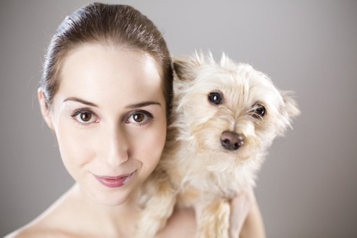 A young woman and her dog reflect each other's appearance.