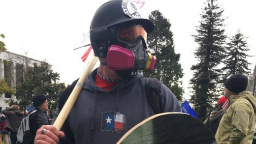 Based Stick Man donning his signature stick at a rally, as well as a helmet, gas mask and shield.