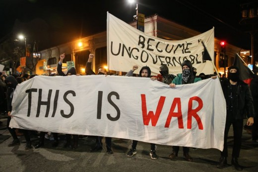 """Antifa and Black Bloc holding signs saying """"Become Ungovernable"""" and """"This Is War""""."""