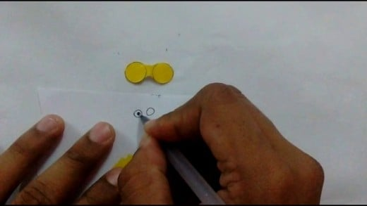 Draw two small white eyes with a black dot in the centre in another paper and cut them out.