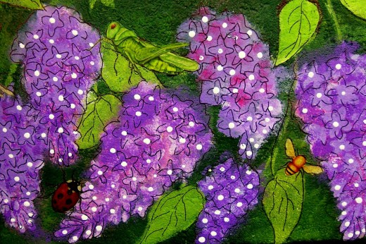 Lilacs painted on a garden rock by nancymaggielee