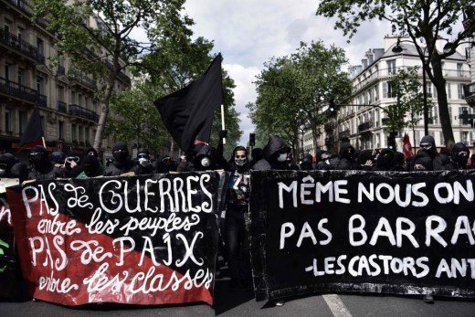 French protestors, wearing all-black and holding an anarcho-communist flag.