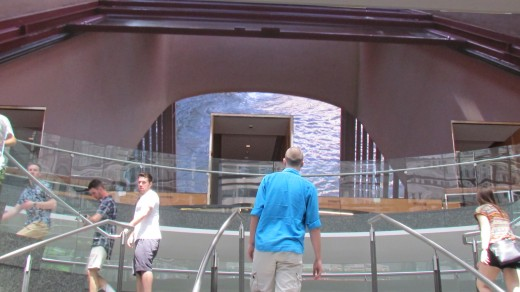 A display of various videos are presented on a wall near the steps with Comcast Center.