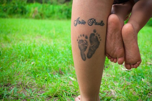A mother wearing her son's birth footprint on the calf of her leg..