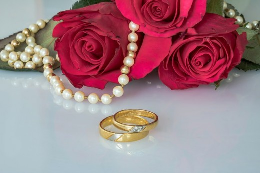 Roses represent love and the gold wedding rings represent a marriage commitment. Weddings do not always have to be white in color. Be creative to bring attention to your product.