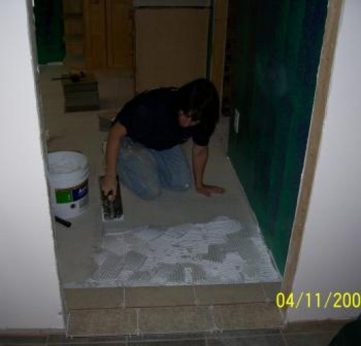 Spreading glue and laying floor tiles