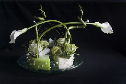 A modern flower arrangement of white calla lilies are accented with wired pearls and exposed stem holders in a shallow dish.