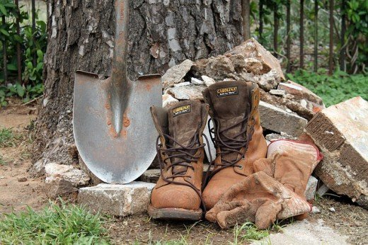 A shovel and a pair of boots as symbols of unskilled labor.