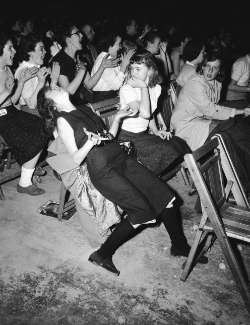 Girl swoons at Elvis Presley concert in 1957.