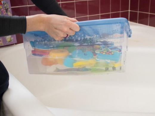 Add all of your bath toys to this prepared mixture, snap on the lid, and shake the container well so that the soap in the mixture agitates, bubbles and envelops the toys.
