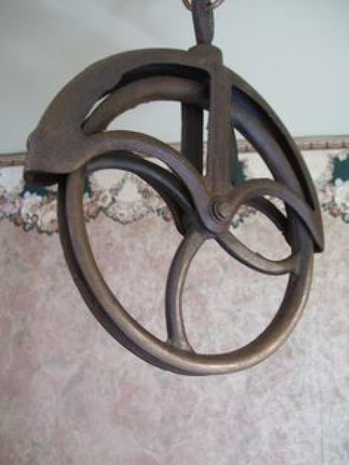 Antique cast iron water well pulley to allow a rope run freely from top to the bottom of the well.