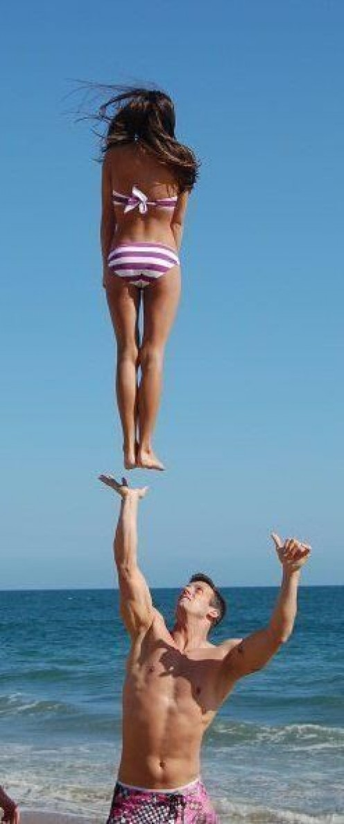 Male female cheerleaders  practice on the  beach.