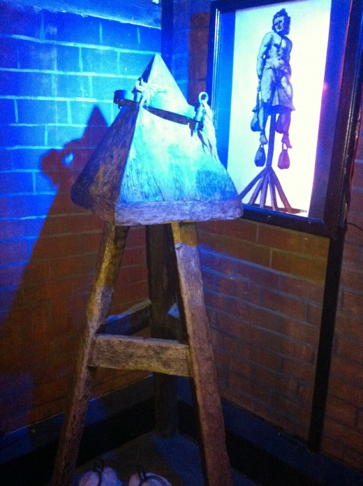 The Judas Cradle would involve the person sitting on the point of the pyramid with weights attached to their arms and legs