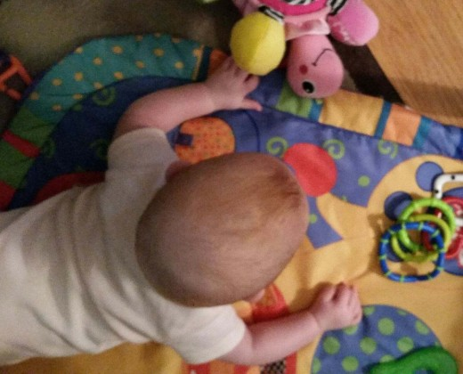 Tummy time is becoming more important for strengthening neck, shoulder and back muscles. Placing articles just out of reach, encourages Imogen to move toward them, by scooting, rolling or crawling.