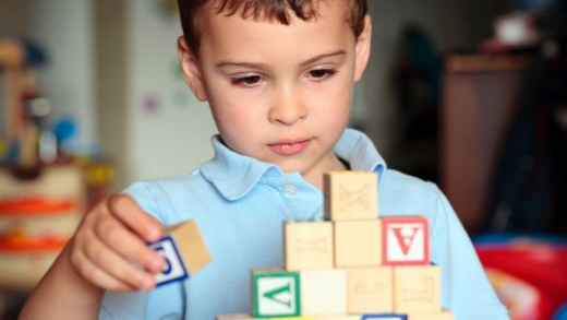 Autistic child stacking blocks.