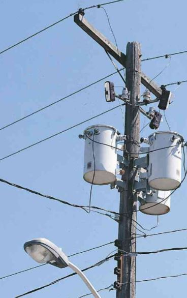 Pole transformer, 20,000 volt feeder lines above go into the transformer primary and the transformer secondary output is 120 volts for local service fed to the lines below.