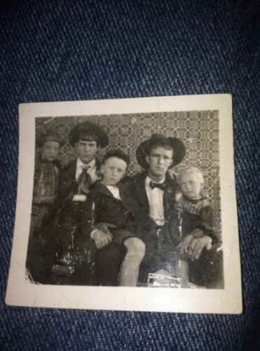 y Grandpa Ballard sitting on his oldest brother Thomas knee, left in photo.