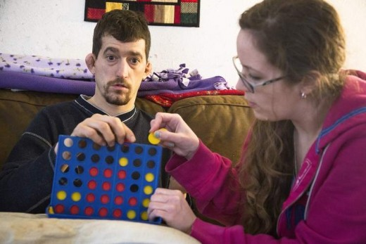 A woman playing Connect Four with a severely autistic adult.