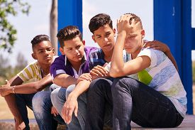 Youth culture young people group of male friends multi-ethnic teens outdoor teenagers together in park. Boys comforting sad friend kids helping depressed boy. Adolescence bond relationship image