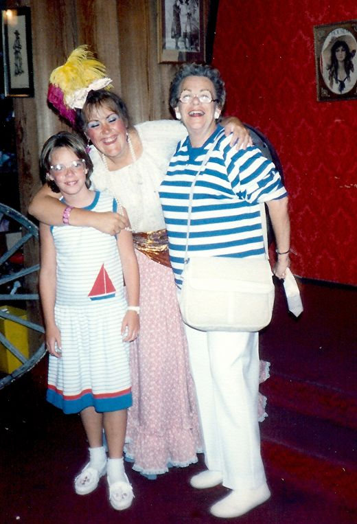 My mother and niece being hugged by a cast member of the Pink Garter Theater.